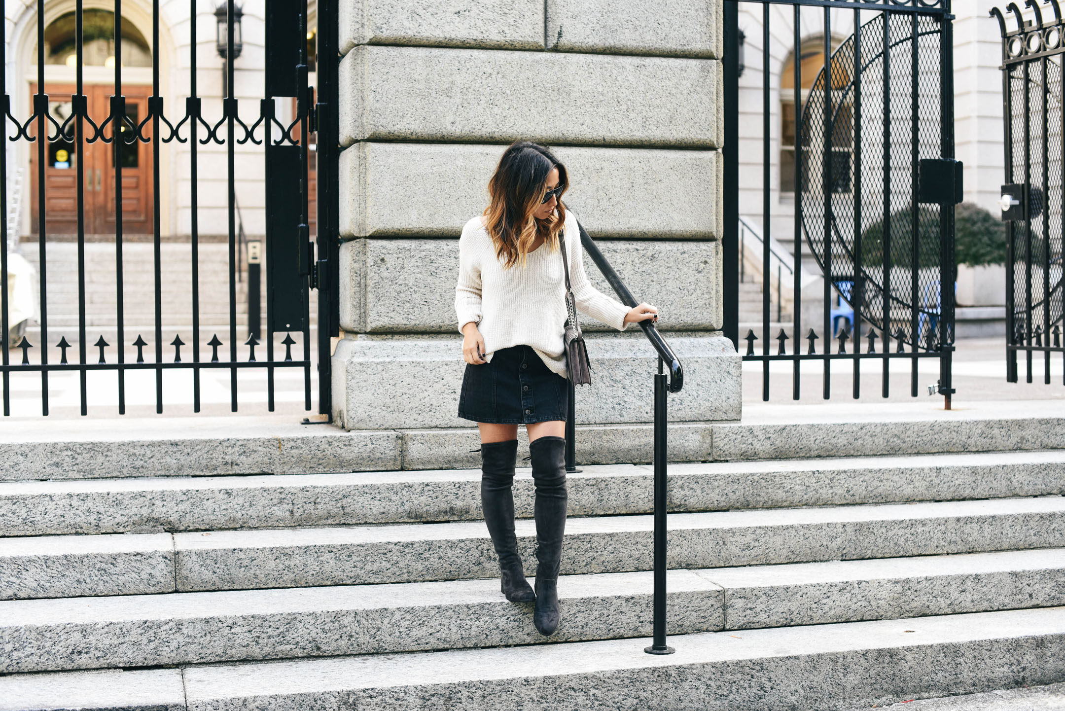 over the knee boots styled with a skirt